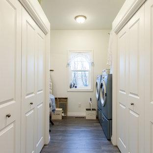 Foto di una sala lavanderia stile shabby di medie dimensioni con ante con bugna sagomata, ante bianche, pareti bianche, lavatrice e asciugatrice affiancate, pavimento in legno massello medio e pavimento marrone
