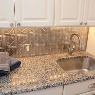 Inspiration for a small traditional single-wall dedicated laundry room in DC Metro with an undermount sink, raised-panel cabinets, white cabinets, granite benchtops, metallic splashback, grey walls, a stacked washer and dryer and grey benchtop.