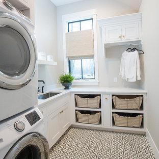 Idéer för mellanstora funkis l-formade vitt tvättstugor enbart för tvätt, med en undermonterad diskho, skåp i shakerstil, vita skåp, bänkskiva i kvarts, grå väggar, betonggolv, en tvättpelare och grått golv