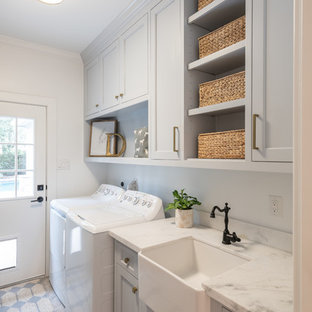 Dedicated laundry room - farmhouse single-wall gray floor dedicated laundry room idea in Houston with a farmhouse sink, recessed-panel cabinets, gray cabinets, white walls and white countertops
