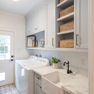 Пример оригинального дизайна: отдельная, прямая прачечная в стиле кантри с раковиной в стиле кантри, фасадами с утопленной филенкой, серыми фасадами, белыми стенами, со стиральной и сушильной машиной рядом, серым полом и белой столешницей