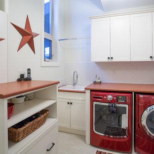 Inredning av en klassisk röda rött tvättstuga, med en nedsänkt diskho och en tvättmaskin och torktumlare bredvid varandra
