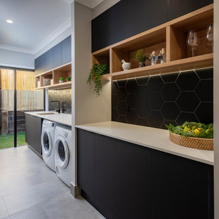 Inredning av en modern tvättstuga, med en nedsänkt diskho, grå väggar, en tvättmaskin och torktumlare bredvid varandra och grått golv