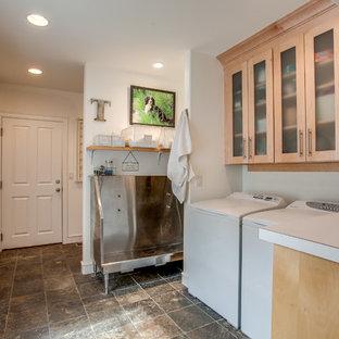 Idéer för en lantlig linjär tvättstuga, med en allbänk, luckor med glaspanel, skåp i ljust trä, vita väggar och en tvättmaskin och torktumlare bredvid varandra