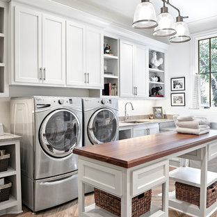 Ispirazione per una grande lavanderia multiuso classica con lavello a vasca singola, ante in stile shaker, ante bianche, top in pietra calcarea, pareti bianche, pavimento in ardesia e lavatrice e asciugatrice affiancate