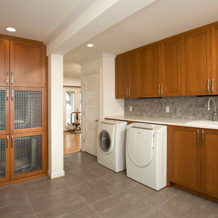 Example of a mid-sized transitional l-shaped porcelain floor utility room design in DC Metro with a drop-in sink, shaker cabinets, medium tone wood cabinets, quartz countertops and white walls