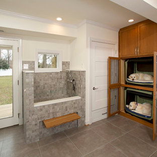 Example of a mid-sized transitional l-shaped porcelain floor utility room design in DC Metro with shaker cabinets, medium tone wood cabinets and white walls