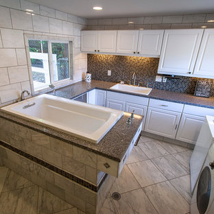 Large classic u-shaped utility room in San Diego with a single-bowl sink, white cabinets, granite worktops, white walls, marble flooring, a side by side washer and dryer and raised-panel cabinets.