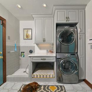 Modelo de lavadero multiusos y lineal, tradicional, de tamaño medio, con pila para lavar, armarios con paneles con relieve, puertas de armario grises, encimera de cuarzo compacto, paredes grises, suelo de baldosas de porcelana, lavadora y secadora apiladas y suelo gris