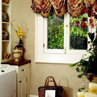 Esempio di una sala lavanderia tradizionale di medie dimensioni con lavello stile country, ante a filo, ante con finitura invecchiata, top in legno, pareti beige, parquet scuro, lavatrice e asciugatrice affiancate, pavimento marrone e top marrone