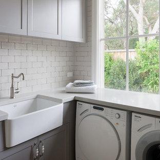 Immagine di una lavanderia multiuso country di medie dimensioni con lavello stile country, ante a filo, ante beige, top in superficie solida e lavatrice e asciugatrice affiancate