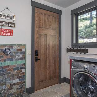 Idéer för rustika grått tvättstugor, med kaklad bänkskiva, vita väggar, en tvättmaskin och torktumlare bredvid varandra och grått golv