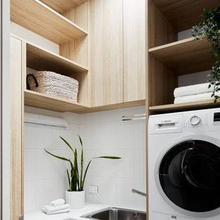 Idéer för en liten modern vita l-formad tvättstuga enbart för tvätt, med en nedsänkt diskho, luckor med profilerade fronter, skåp i ljust trä, marmorbänkskiva, vita väggar, klinkergolv i keramik, en tvättpelare och vitt golv