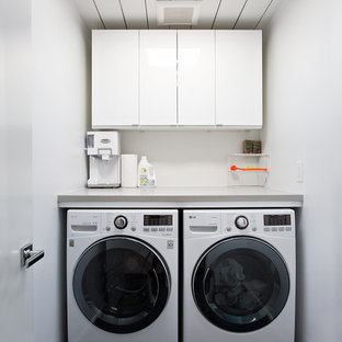 This is an example of a small midcentury single-wall dedicated laundry room in San Francisco with flat-panel cabinets, white cabinets, white walls, a side-by-side washer and dryer, black floor and grey benchtop.