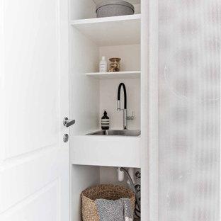 Inspiration för en liten funkis vita linjär vitt liten tvättstuga, med en nedsänkt diskho, vita skåp, bänkskiva i koppar, vitt stänkskydd, stänkskydd i keramik, vita väggar, klinkergolv i porslin, en tvättpelare och vitt golv