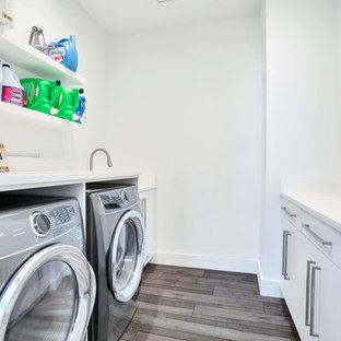 Esempio di una sala lavanderia industriale di medie dimensioni con lavello sottopiano, ante in stile shaker, ante bianche, pareti bianche, lavatrice e asciugatrice affiancate, pavimento grigio e top bianco