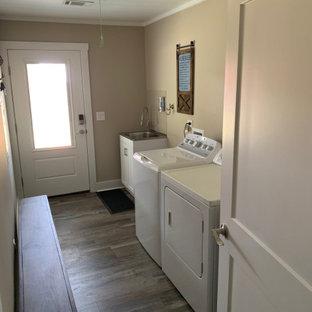 Ispirazione per una sala lavanderia country di medie dimensioni con ante bianche, pareti beige, pavimento in laminato, lavatrice e asciugatrice affiancate e soffitto in perlinato