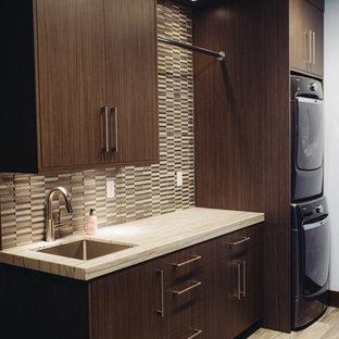 Klassisk inredning av en mellanstor l-formad tvättstuga enbart för tvätt, med en undermonterad diskho, skåp i mörkt trä, en tvättpelare, släta luckor, marmorbänkskiva, flerfärgade väggar och mörkt trägolv
