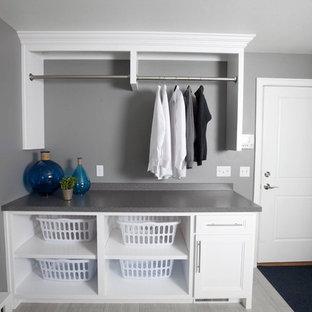 Esempio di una lavanderia multiuso moderna con ante con riquadro incassato, ante bianche, top in laminato e pareti grigie
