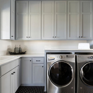Large beach style l-shaped separated utility room in Minneapolis with a built-in sink, grey cabinets, engineered stone countertops, white walls, ceramic flooring, a side by side washer and dryer, black floors, white worktops and shaker cabinets.