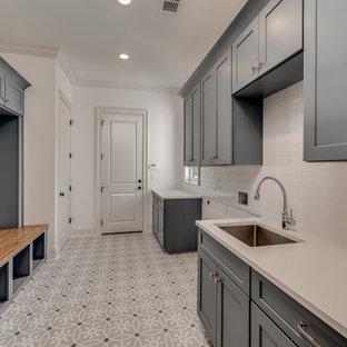 Inspiration för stora medelhavsstil parallella vitt grovkök, med en undermonterad diskho, skåp i shakerstil, grå skåp, bänkskiva i kvarts, vitt stänkskydd, stänkskydd i porslinskakel, vita väggar, klinkergolv i terrakotta, en tvättmaskin och torktumlare bredvid varandra och flerfärgat golv