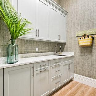 Immagine di una grande lavanderia tropicale con lavello sottopiano, ante a filo, ante bianche, top in quarzite, paraspruzzi con piastrelle di vetro, parquet chiaro, pavimento marrone e top beige