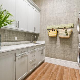 Inredning av en exotisk stor beige u-formad beige tvättstuga, med en undermonterad diskho, luckor med profilerade fronter, vita skåp, bänkskiva i kvartsit, blått stänkskydd, stänkskydd i glaskakel, ljust trägolv och brunt golv