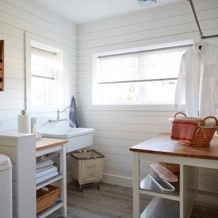 Inspiration för en stor maritim tvättstuga enbart för tvätt, med en rustik diskho, öppna hyllor, vita skåp, träbänkskiva, vita väggar, laminatgolv, en tvättmaskin och torktumlare bredvid varandra och grått golv