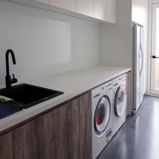 Foto di una grande lavanderia multiuso design con lavello da incasso, ante in legno scuro, top in cemento, pareti bianche, pavimento in cemento, lavatrice e asciugatrice affiancate, pavimento nero e top bianco