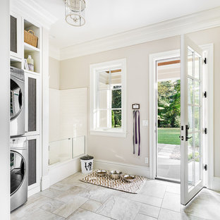 Design ideas for a large classic utility room in Chicago with white cabinets, beige walls, ceramic flooring, a stacked washer and dryer and grey floors.