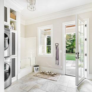 シカゴの広いトランジショナルスタイルのおしゃれな家事室 (白いキャビネット、ベージュの壁、セラミックタイルの床、上下配置の洗濯機・乾燥機、グレーの床) の写真