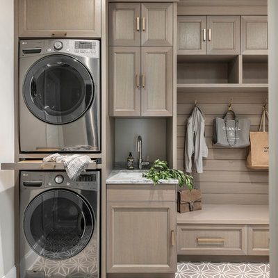 Mid-sized transitional single-wall beige floor utility room photo in Chicago with recessed-panel cabinets, gray cabinets, quartzite countertops, gray backsplash, stone slab backsplash, gray countertops, an undermount sink, beige walls and a stacked washer/dryer