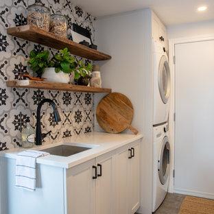 Idéer för små vintage linjära vitt tvättstugor enbart för tvätt, med en enkel diskho, skåp i shakerstil, vita skåp, bänkskiva i kvarts, flerfärgad stänkskydd, stänkskydd i porslinskakel, flerfärgade väggar, klinkergolv i porslin, en tvättpelare och grått golv