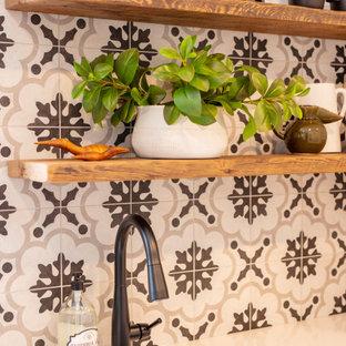Bild på en liten vintage vita linjär vitt tvättstuga enbart för tvätt, med en enkel diskho, skåp i shakerstil, vita skåp, bänkskiva i kvarts, flerfärgad stänkskydd, stänkskydd i porslinskakel, flerfärgade väggar, klinkergolv i porslin, en tvättpelare och grått golv