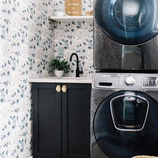 Immagine di una lavanderia nordica con lavello sottopiano, ante in stile shaker, ante nere, pareti multicolore, lavatrice e asciugatrice a colonna, pavimento grigio e top bianco