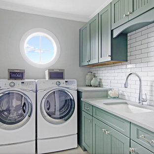 Dedicated laundry room - small beach style l-shaped dedicated laundry room idea in Jacksonville with an undermount sink, recessed-panel cabinets, a side-by-side washer/dryer, gray countertops and blue cabinets