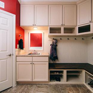 Cette photo montre une buanderie chic en U multi-usage et de taille moyenne avec un évier 1 bac, un placard avec porte à panneau encastré, des portes de placard blanches, un mur rouge, un sol en carrelage de porcelaine, des machines côte à côte, un sol marron et un plan de travail beige.