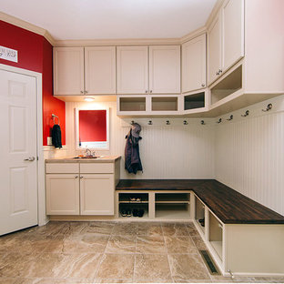 Immagine di una lavanderia multiuso chic di medie dimensioni con lavello a vasca singola, ante con riquadro incassato, ante bianche, pareti rosse, pavimento in gres porcellanato, lavatrice e asciugatrice affiancate, pavimento marrone e top beige