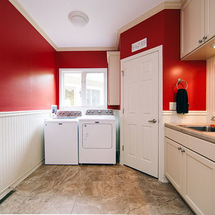 This is an example of a mid-sized transitional u-shaped utility room in Other with a single-bowl sink, recessed-panel cabinets, white cabinets, red walls, porcelain floors, a side-by-side washer and dryer, brown floor and beige benchtop.