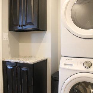 Ispirazione per una sala lavanderia chic di medie dimensioni con ante con bugna sagomata, ante con finitura invecchiata, top in granito, pareti beige e lavatrice e asciugatrice a colonna