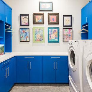 Inspiration för en funkis vita u-formad vitt tvättstuga enbart för tvätt, med släta luckor, blå skåp, vita väggar och en tvättmaskin och torktumlare bredvid varandra