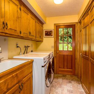 Inspiration för stora lantliga parallella grovkök, med en nedsänkt diskho, luckor med upphöjd panel, skåp i mellenmörkt trä, laminatbänkskiva, gula väggar och en tvättmaskin och torktumlare bredvid varandra