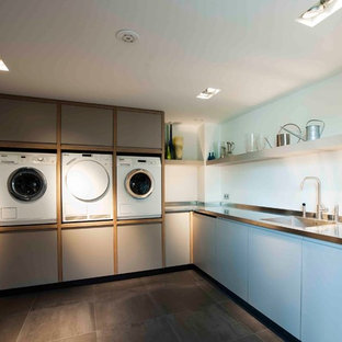 Utility room - large contemporary l-shaped utility room idea in New York with an integrated sink, stainless steel countertops, white walls, flat-panel cabinets and blue cabinets