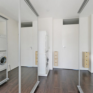 Small trendy galley plywood floor dedicated laundry room photo in Amsterdam with glass-front cabinets, white cabinets, beige walls and a stacked washer/dryer