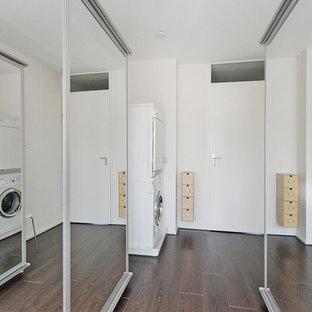 Bild på en liten funkis parallell tvättstuga enbart för tvätt, med luckor med glaspanel, vita skåp, beige väggar, plywoodgolv och en tvättpelare