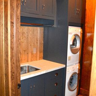 Foto di una sala lavanderia stile rurale di medie dimensioni con lavello sottopiano, ante in stile shaker, ante blu, top in superficie solida, pareti marroni, pavimento con piastrelle in ceramica e lavatrice e asciugatrice a colonna