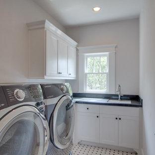 Idéer för en mellanstor klassisk blå tvättstuga enbart för tvätt, med en enkel diskho, vita skåp, vita väggar, klinkergolv i keramik, en tvättmaskin och torktumlare bredvid varandra och flerfärgat golv