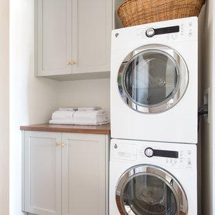 Idee per un piccolo ripostiglio-lavanderia moderno con ante in stile shaker, pareti bianche, pavimento in pietra calcarea, lavatrice e asciugatrice a colonna, pavimento beige, ante grigie e top in legno