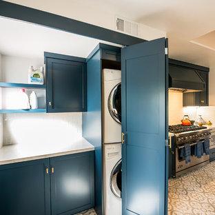 Idées déco pour une petit buanderie linéaire contemporaine dédiée avec un placard à porte shaker, des portes de placard bleues, un plan de travail en quartz, un mur blanc, un sol en carrelage de céramique, des machines superposées et un sol blanc.
