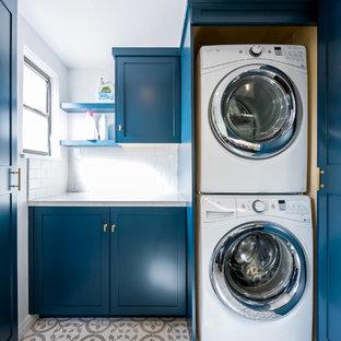 Immagine di una piccola sala lavanderia minimal con ante in stile shaker, ante blu, top in quarzite, pareti bianche, pavimento con piastrelle in ceramica, lavatrice e asciugatrice a colonna e pavimento bianco